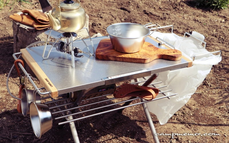 ユニフレームの焚き火テーブルにスノーピークのガビングフレーム、IKEAの取ってバッガネースとレンプリング(鍋敷き)を取り付け